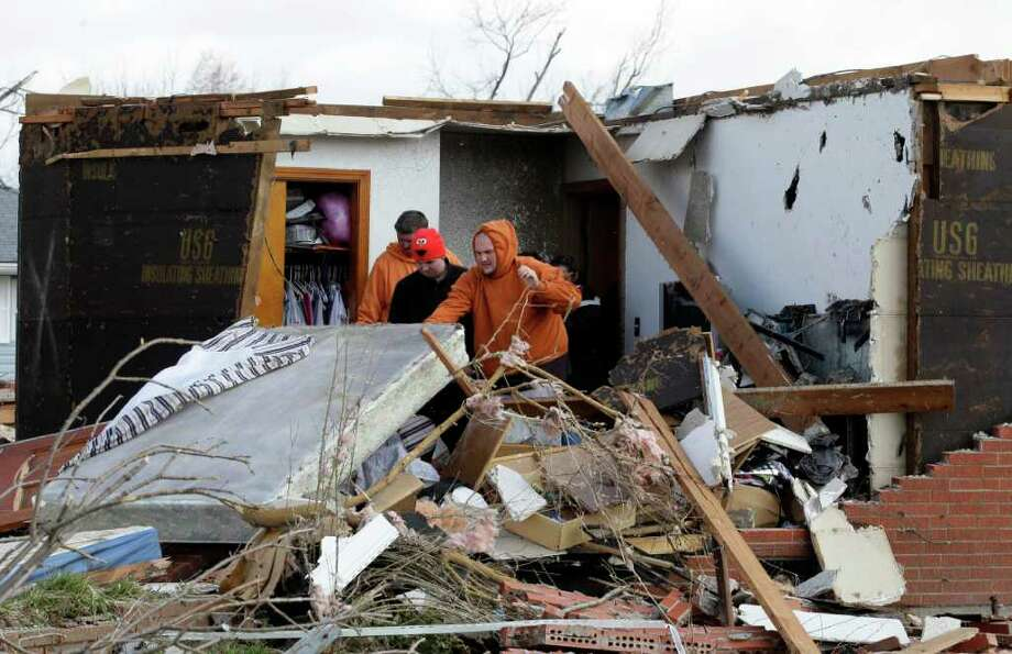 Residents clean up their damaged house in Marysville, Ind., Saturday, March 3, 2012. Massive thunderstorms, predicted by forecasters for days, threw off dozens of tornadoes as they raced Friday from the Gulf Coast to the Great Lakes. Twisters crushed blocks of homes, knocked out cellphones and landlines, ripped power lines from broken poles and tossed cars, school buses and tractor-trailers onto roads made impassable by debris. (AP Photo/Nam Y. Huh) Photo: Nam Y. Huh