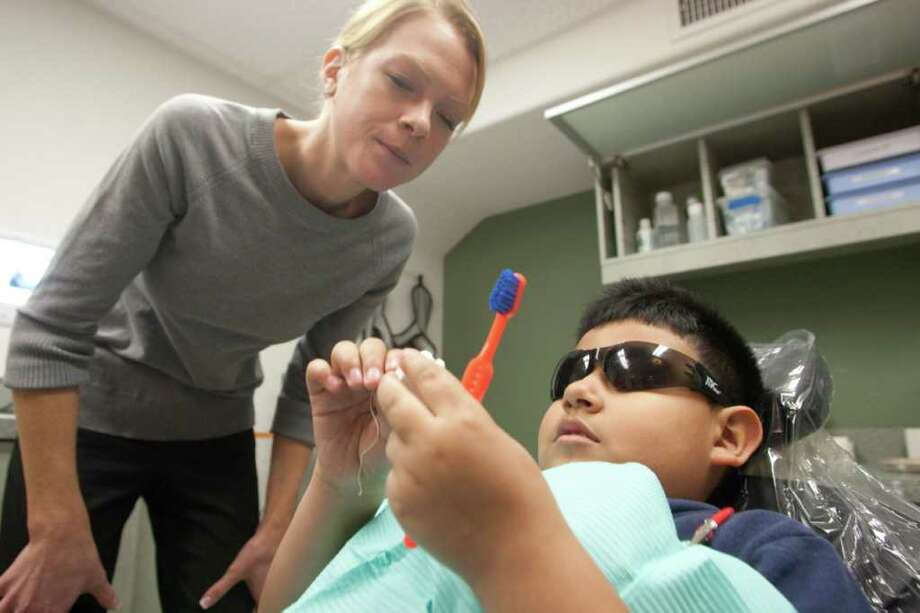 University of Texas School of Dentistry student Bethany Petersen shows Luis Avalos, 9, how to brush his teeth at the Denver Harbor Clinic. Photo: Patric Schneider / Houston Chronicle