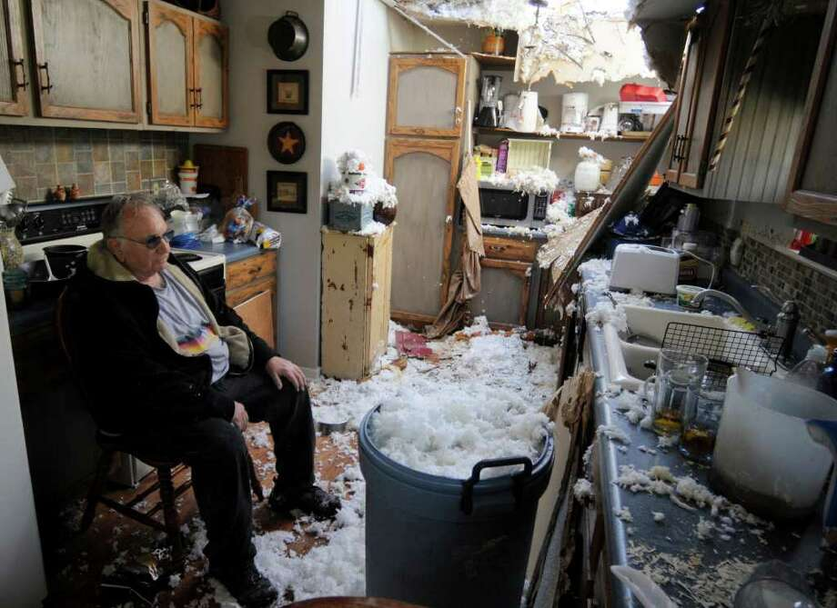 Robert Elliott sits in his damaged kitchen Saturday after a tornado struck his home in Harrison, Tenn. Emergency crews searched for injured victims. Photo: Billy Weeks / FR67639 AP