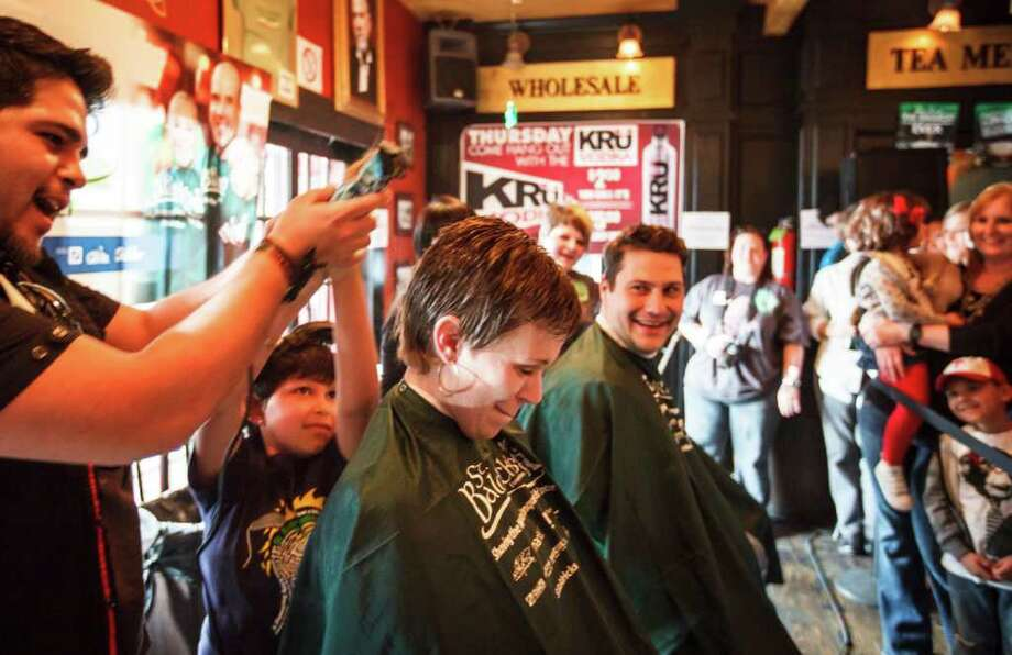 Wendi Schoffstall has her head shaved by Jason Mikeasky and Emily Pena, 7, as Greg Kopacz looks on during the St. Baldrick's Foundation Head-Shaving Event to raise funds for kids with cancer at Brian O'Neill's Irish Pub, Saturday, March 3, 2012, in Houston. Pearland-resident Emily Pena , 7, is one of five St. Baldrick's 2012 Ambassador Kids, and was diagnosed with acute lymphoblastic leukemia at age 5. Photo: Michael Paulsen, Houston Chronicle / © 2012 Houston Chronicle