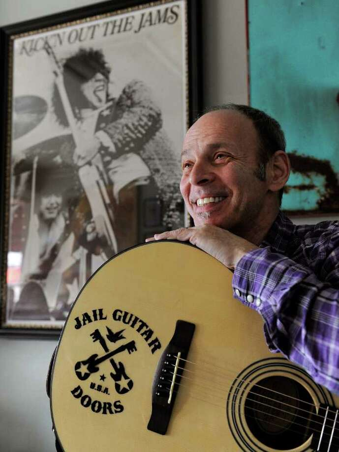 In this Jan. 16, 2012 photo, guitarist Wayne Kramer, founder of the band the MC5, poses with one of the instruments that will be provided to jail inmates as part of the Jail Guitar Doors USA initiative at his recording studio in Los Angeles. The Jail Guitar Doors program provides instruments to inmates who are using music as a means of achieving rehabilitation. (AP Photo/Chris Pizzello) Photo: Chris Pizzello / AP2012