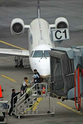 Passengers prepare to board a United Express plane before departing from Albany International Airport on Wednesday Feb. 15, 2012 in Colonie, NY.  (Philip Kamrass / Times Union ) Photo: Philip Kamrass / 00016453A