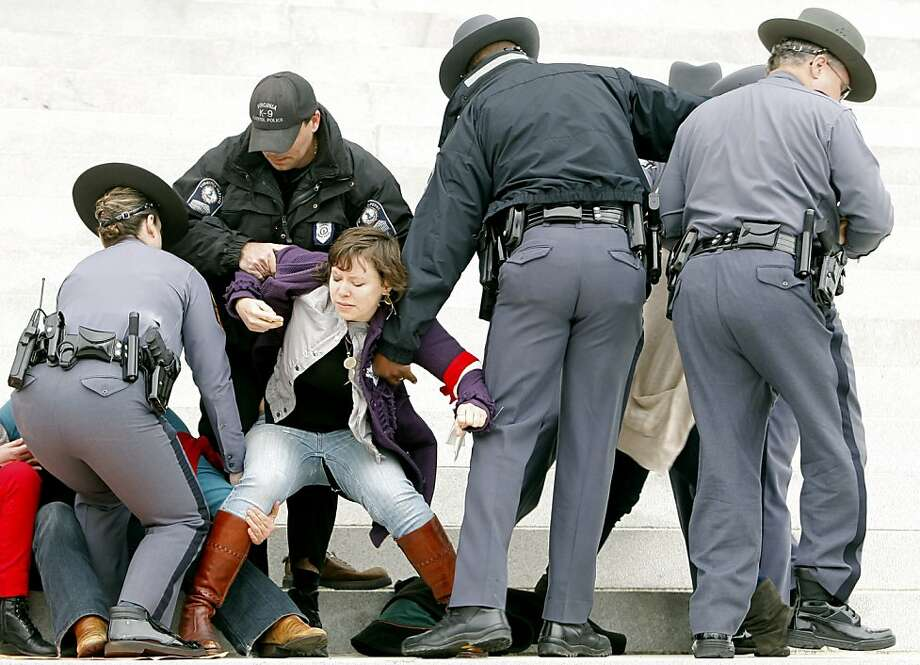 Protesters are removed from the front steps of the State Capitol in Richmond, Va., Saturday, March 3, 2012. Virginia Capitol Police arrested more than 30 women's rights activists Saturday when they refused to leave the Capitol steps during a protest of anti-abortion legislation. The protesters were some of an estimated 500 who had marched down a downtown street before gathering on the Capitol grounds to protest legislation like a bill that passed the General Assembly earlier in the week that requires an ultrasound before an abortion.  (AP Photo/Richmond Times-Dispatch, Eva Russo) Photo: Eva Russo, Associated Press