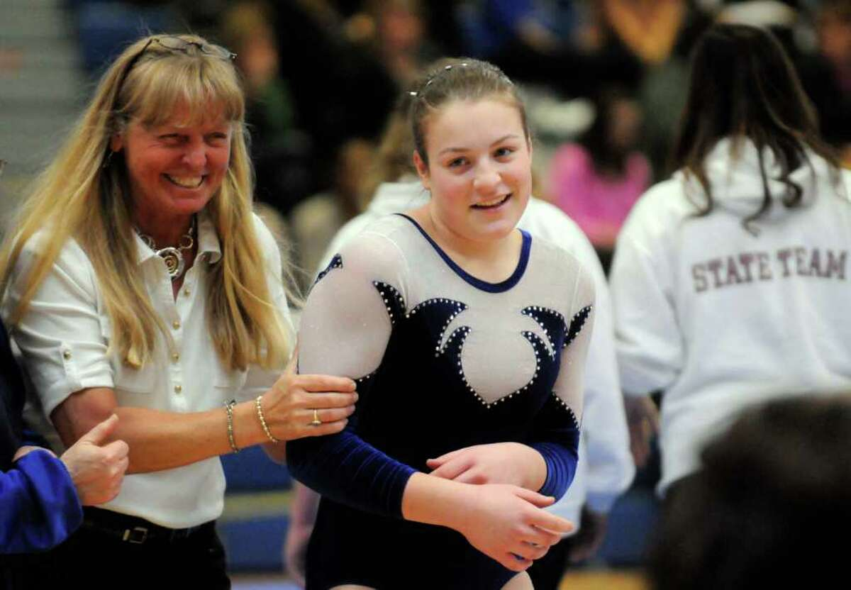 Shaker coach Marbry Gansle, left, congratulates Stefanie Miller after her beam routine in the state gymnastics meet at Shaker High School in Colonie, N.Y. Saturday March 3, 2012.( Michael P. Farrell/Times Union)