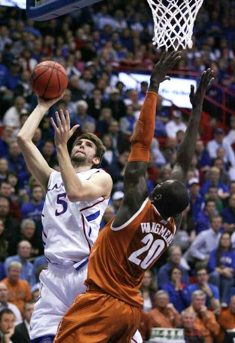 Kansas' Jeff Withey, left, takes a shot over Texas' Alexis Wangmene in the first half. In the second half, Wangmene left the game after hurting his wrist in a fall. Photo: Ed Zurga / FR34145 AP