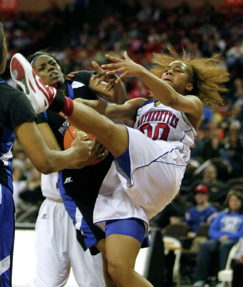 Duncanville's Kiara Perry, right, and Dekaney's Kayla Nevitt fight for a rebound in the girls Class 5A state championship game in Austin on Saturday. The Pantherettes won 69-31 for their seventh championship in program history, ending the Panthers' school-record playoff run. Photo: Erich Schlegel / ©2012 Erich Schlegel