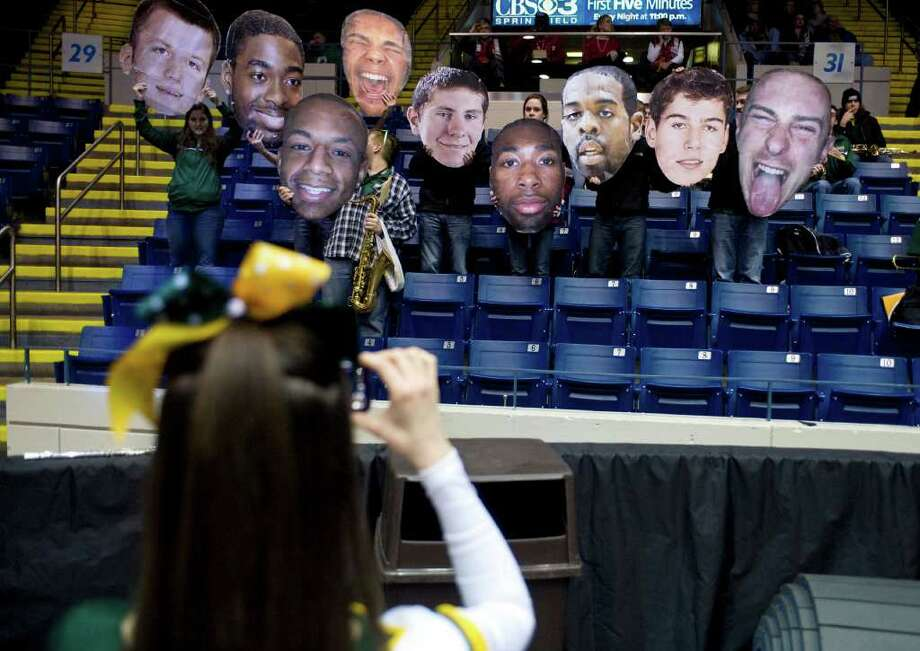 A cheerleader takes a photo of the band holding cut-outs of players before a MAAC men's quarterfinals college basketball game between Siena and Manhattan in Springfield, Mass., Saturday, March 3, 2012. (Jessica Hill / Special to the Times Union) Photo: Jessica Hill