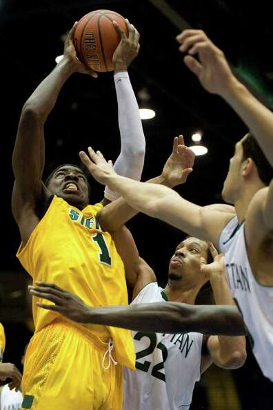Siena's OD Anosike, left, is guarded by Manhattan's Roberto Colonette, center, and Emmy Andujar, rig