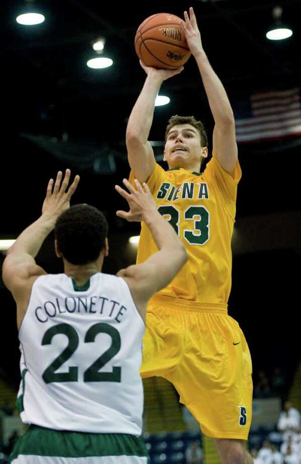Siena's Rob Poole, right, shoots a basket over Manhattan's Roberto Colonette, left, in the first half of a MAAC men's quarterfinals college basketball game in Springfield, Mass., Saturday, March 3, 2012. (Jessica Hill / Special to the Times Union) Photo: Jessica Hill