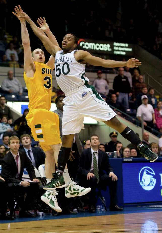 Siena's Owen Wignot, left, follows through on the tying basket, forcing overtime as Manhattan's Kidani Brutus, right, defends at the end of the second half of a MAAC men's quarterfinal college basketball game in Springfield, Mass., Sunday, March 4, 2012. (Jessica Hill / Special to the Times Union) Photo: Jessica Hill
