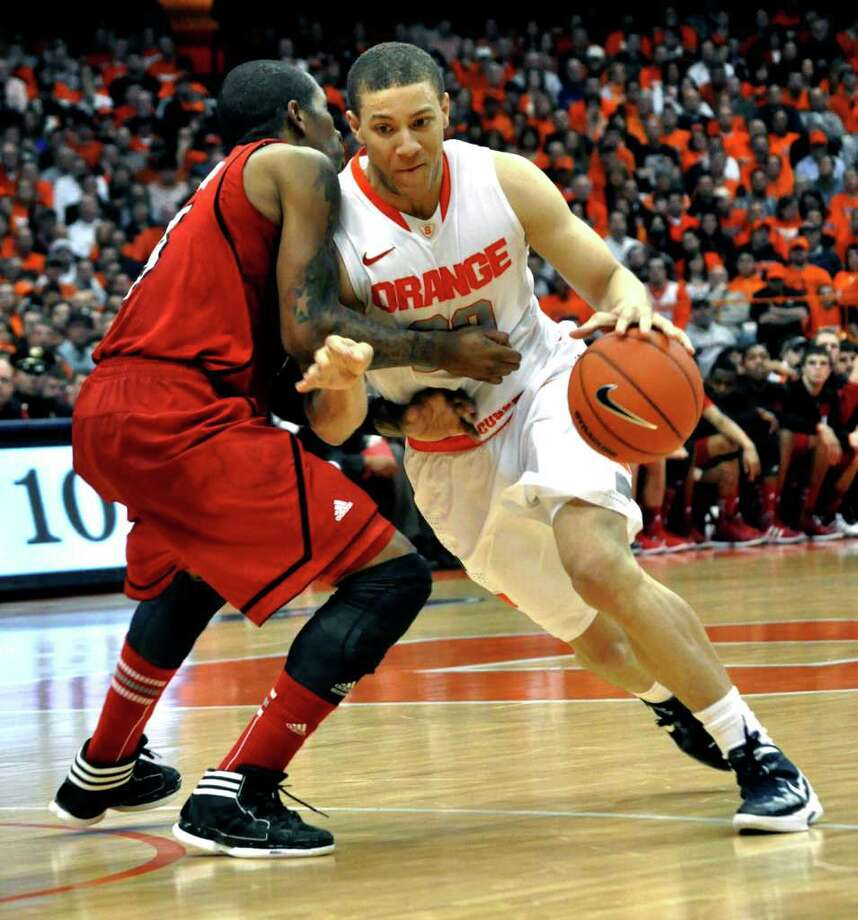 Syracuse's Brandon Triche, right, drives against Louisville's Chris Smith during the second half of an NCAA college basketball game in Syracuse, N.Y., Saturday, March 3, 2012. Syracuse won 58-49. (AP Photo/Kevin Rivoli) Photo: Kevin Rivoli