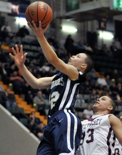 Cohoes' #12, Elijah Newsome, left, gets past 'Vliet defenders during the Section II Class B boys' ba