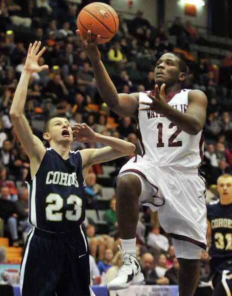 Watervliet's #12, Antoine Johnson goes up for two past Cohoes' # 23 Brandon LaForest, left,  in the