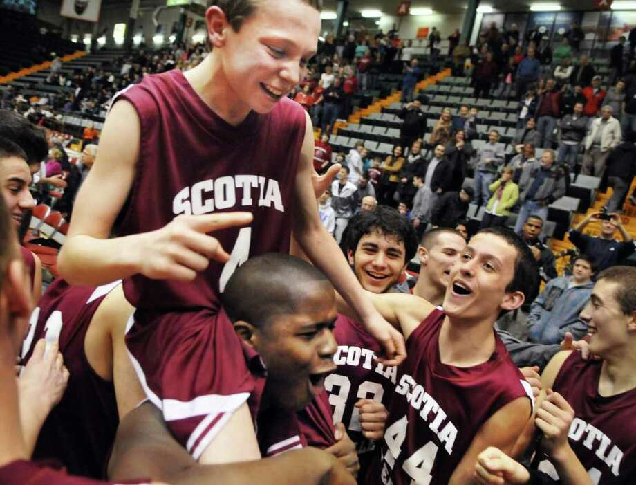 Scotia's #4 freshman Scot Stopera is carried on the shoulders of teammate John Kely as they celebrate their win over Bishop Gibbons in the Section II Class A boys' basketball final at the Glens Falls Civic Center Saturday March 3, 2012.    (John Carl D'Annibale / Times Union) Photo: John Carl D'Annibale / 00016625A