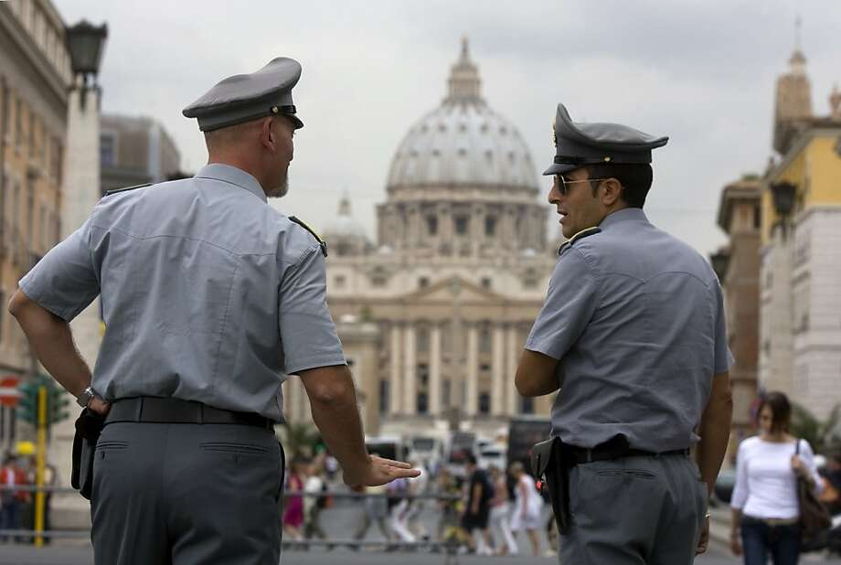 FILE - In this Tuesday, Sept. 21, 2010 file photo Italian financial Police officers talk, in front of St. Peter's square at the Vatican.    The Vatican is being besieged by near-daily leaks of confidential documents and tabloid-style reports about alleged money laundering at the Vatican bank, and in news reports Saturday Feb. 11, 2012, some conspiracy theorists highlight the upcoming crowning of 22 new cardinals, who will be partly responsible for electing the successor to the Pope himself. (AP Photo/Angelo Carconi, File) Photo: Angelo Carconi, Associated Press