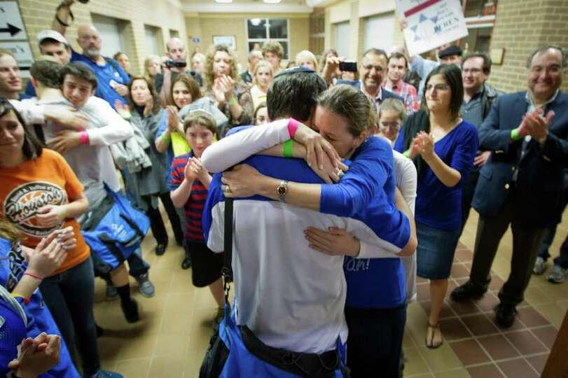 A crowd of supporters applauds as Beren Academy post Ahron Guttman is hugged by his mother Dorit Gut