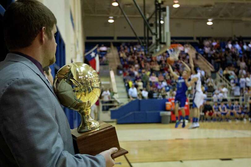 A TAPPS official stands in the wings with the championship trophy as Abilene Christian guard Ben Geo