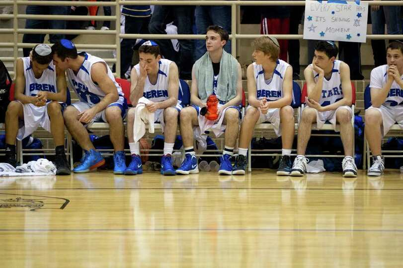 Beren Academy players sit on the bench during the fourth quarter.