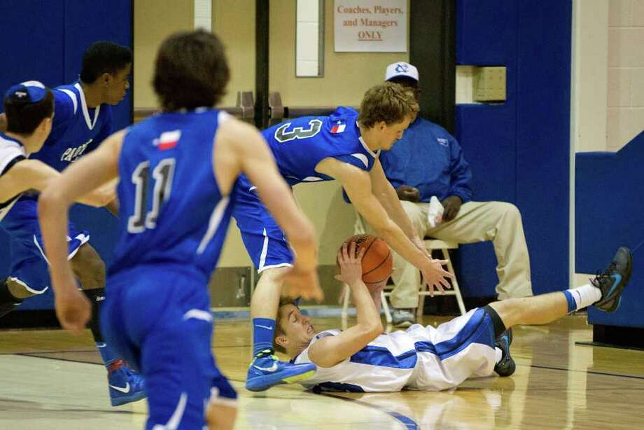 Beren Academy guard Isaac Mirwis struggles to keep the ball as he hits the floor while defended by Abilene Christian guard Ben George. Photo: Smiley N. Pool, Houston Chronicle / © 2012  Houston Chronicle