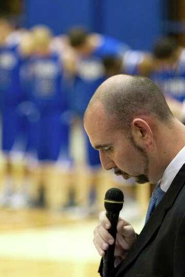 Beren Academy head coach Chris Cole delivers a prayer before facing Abilene Christian