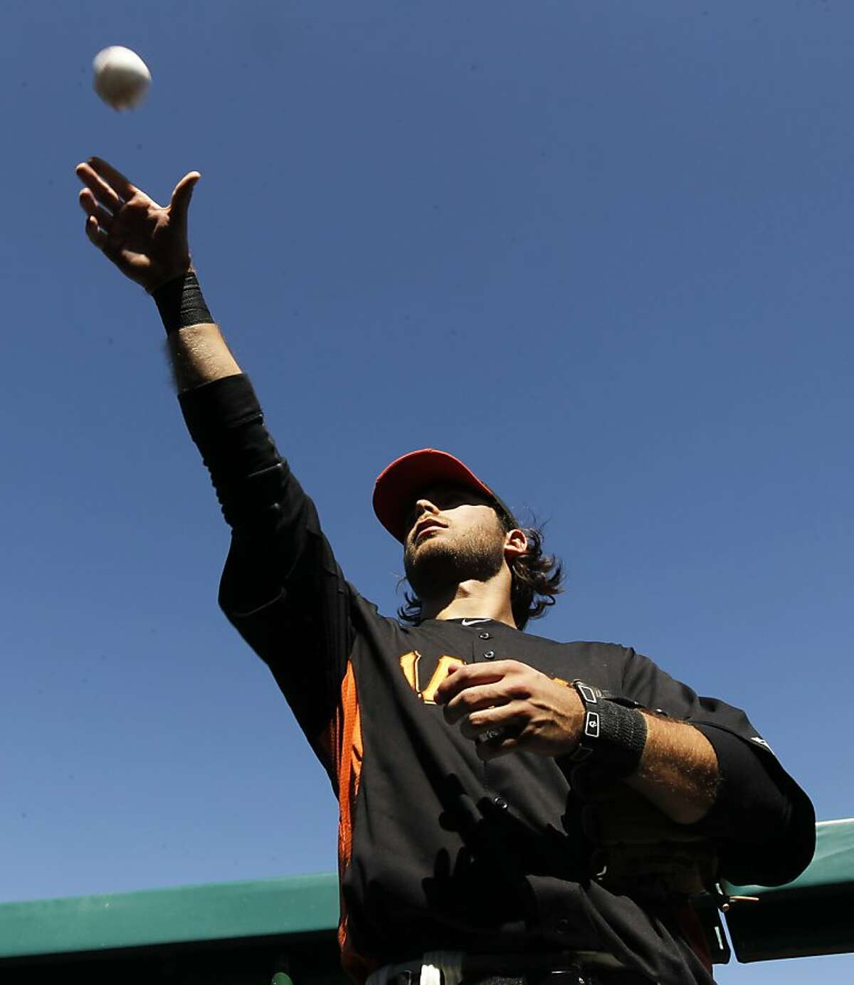Brandon Crawford tosses an autographed baseball back to a fan before the San Francisco Giants Cactus League spring training opener against the Arizona Diamondbacks in Scottsdale, Ariz. on Saturday, March 3, 2012.