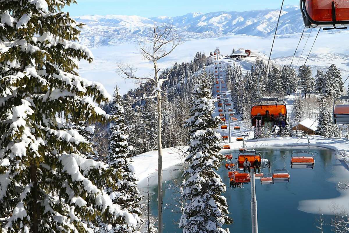 The Orange Bubble Express carries passengers over the snow making pond at Canyons Resort, Utah.
