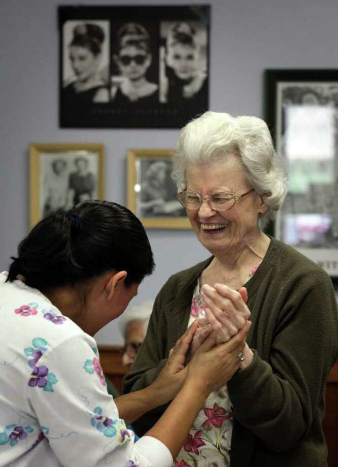 Jeanet B. (right) enjoys a dance with certified nursing assistant Diana Lozano at Grace Place, an Alzheimer's activity center. The center has been seeing an increase in baby boomers in recent months. The facility is redeveloping its program to meet the activities to address the issue. Photo: BOB OWEN, San Antonio Express-News / © 2012 San Antonio Express-News