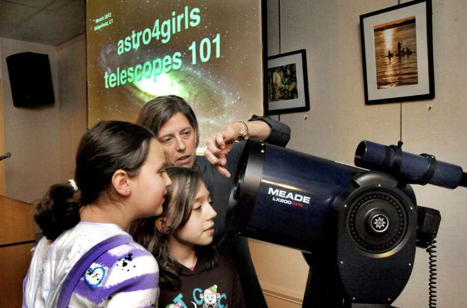 Planatary astronomer Heidi Hammel talks about telescopes with Gillian Stone, 11, left, and Makenzi Macko, 10, during a program at the Ridgefield Library Saturday, March 3, 2012. Both girls are part of the Astro 4 Girls project. Photo: Michael Duffy / The News-Times