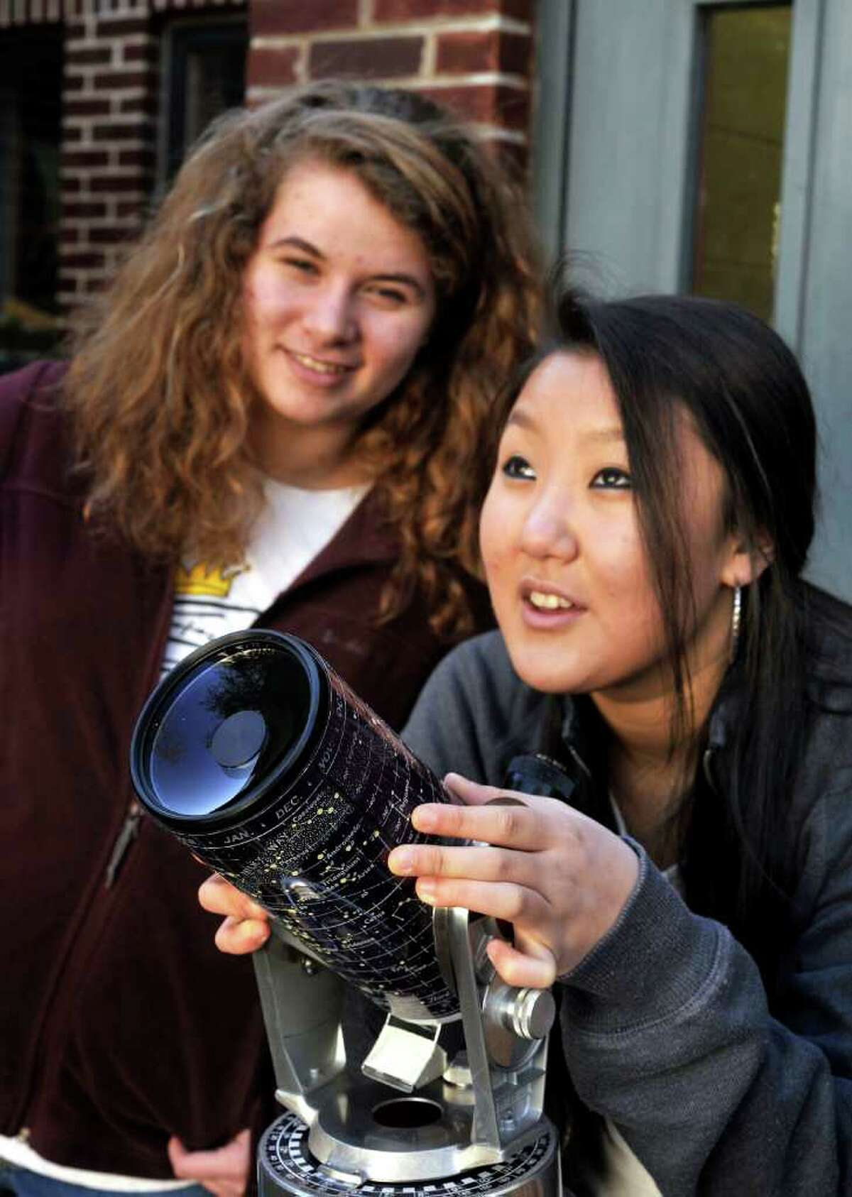Sierra Schafer, left, and Esther Kim, both 15, look for the moon outside the Ridgefield Library during Planatary astronomer Heidi Hammel's talk about telescopes Saturday, March 3, 2012.