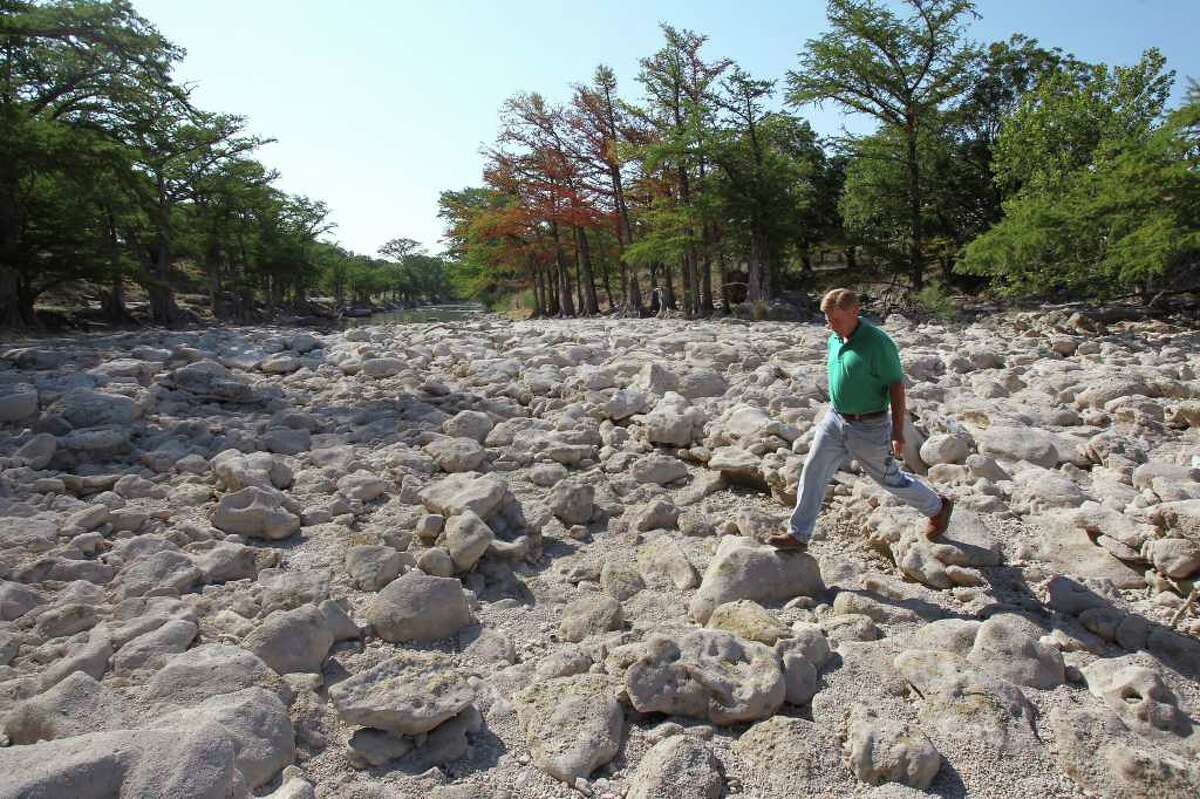 Dry in 2011: Barnett strides across rocks in the Guadalupe near FM 311 and the River Point subdivision, upstream from Canyon Lake, last June amid Texas' record-setting drought.
