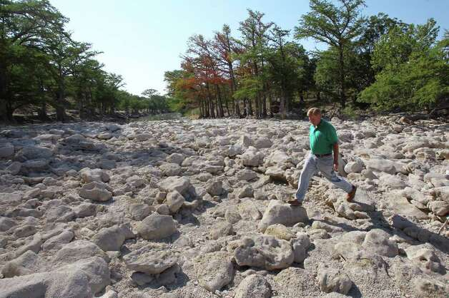 Dry in 2011: Barnett strides across rocks in the Guadalupe near FM 311 and the River Point subdivision, upstream from Canyon Lake, last June amid Texas' record-setting drought. Photo: TOM REEL, San Antonio Express-News / © 2011 San Antonio Express-News