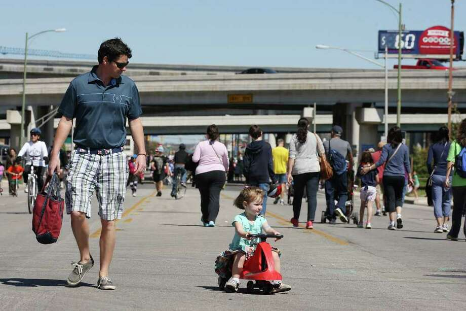 METRO -- Clay Carrington walks siclovia along with his daughter, Sloan, 2, on Broadway Street, Sunday, March 4, 2012. Jerry Lara/San Antonio Express-News Photo: Jerry Lara, San Antonio Express-News / © 2012 San Antonio Express-News