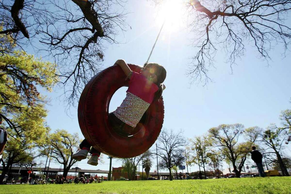 METRO -- Carena Soberal, 5, (cq on both), swings on a tire provided for the public during siclovia at Maverick Park along Broadway Street, Sunday, March 4, 2012. Thousands of pedestrians and cyclist participated in the event. Jerry Lara/San Antonio Express-News
