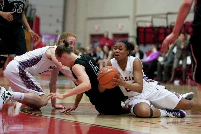 Adrienne Jones (right) of UAlbany gathers a loose ball on the floor, during an America East Semifina