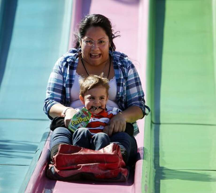 Anastacio Quijada, 3, looks like a Superslide pro at the rodeo carnival. But his aunt Cristina Quijada seems a bit on edge. (James Nielsen / Chronicle)