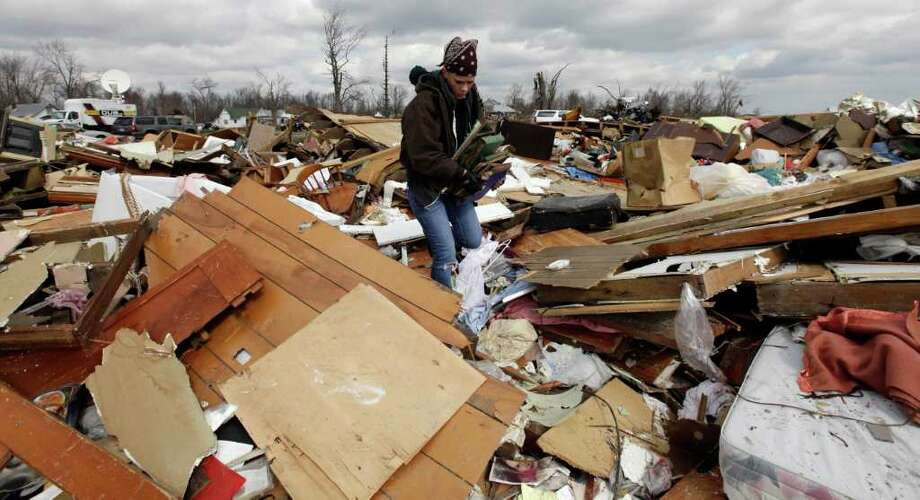 Christa Suchowski search through a home destroyed by a tornado in Marysville, Ind., Sunday, March 4, 2012. Calm weather gave dazed residents of storm-wracked towns a respite on Sunday as they dug out from a chain of tornadoes that cut a swath of destruction from the Midwest to the Gulf of Mexico, killing at least 39 people. (AP Photo/Nam Y. Huh) Photo: Nam Y. Huh / AP