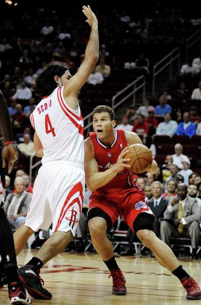Los Angeles Clippers' Blake Griffin, right, looks for room around Houston Rockets' Luis Scola (4) in