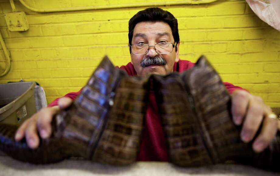 Jorge Miscles, of Juarez, Mexico, makes sure a pair of boots he's making are symmetrical Thursday, Feb. 10, 2011, in the Stallion Boots and Leather Goods facility in El Paso. Photo: Nick De La Torre, Houston Chronicle / Houston Chronicle