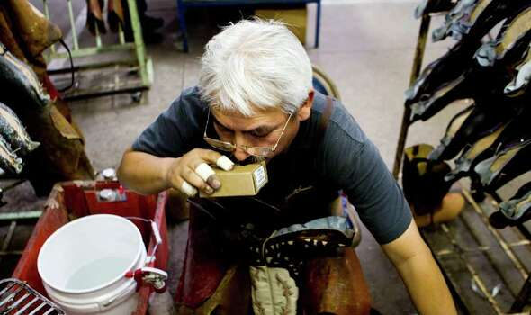 Pedro Lopez fills his mouth with nails as he quickly puts leather around the toe box of a pair of boots Wednesday, Feb. 9, 2011, in the Lucchese Boot Company's factory in El Paso. Lopez is a third generation boot maker and has worked with Lucchese for 23-years. Photo: Nick De La Torre, Houston Chronicle / Houston Chronicle