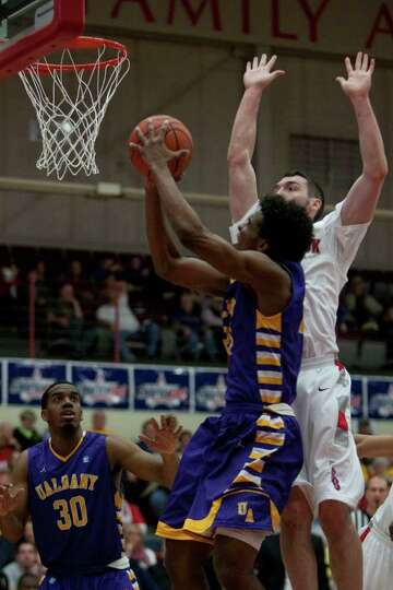 Gerardo Suero of UAlbany drives to the hoop as he is defended by Tommy Brenton of Stony Brook, durin