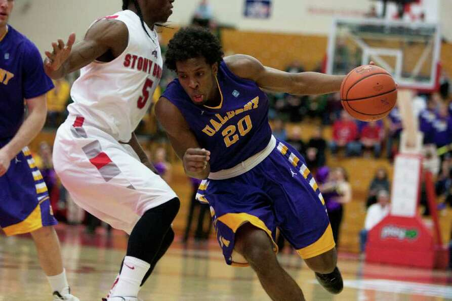 Gerardo Suero of UAlbany drives to the hoop as he is defended by Dave Coley of Stony Brook, during t