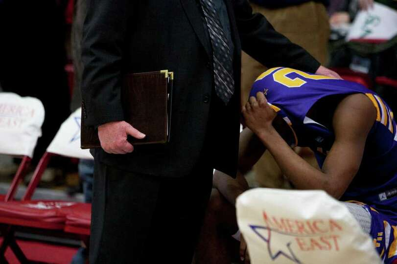 Gerardo Suero of UAlbany sits alone in tears on the bench after Stony Brook edges the Great Danes at