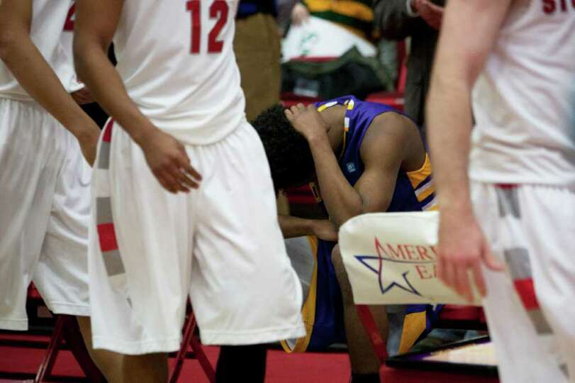 Gerardo Suero (center) of UAlbany sits alone in tears on the bench after Stony Brook edges the Great