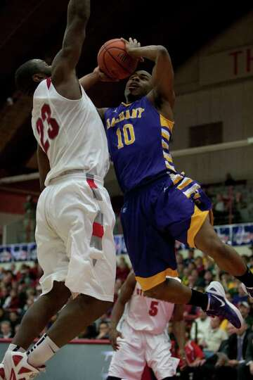 Mike Black of UAlbany (right) attempts a layup as he is defended by Dallis Joyner of Stony Brook, du