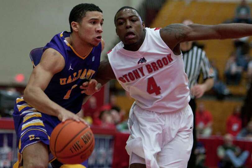 Tanner Gibson of UAlbany (left) drives down the right against Anthony Jackson (right) of Stony Brook