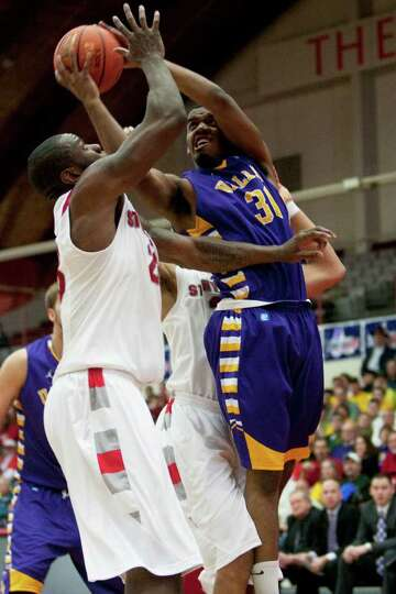 Jayson Guerrier of UAlbany (right) attempts a layup as he is defended by Dallis Joyner of Stony Broo