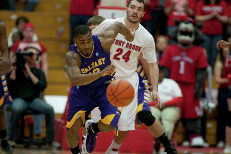 Mike Black of UAlbany runs after a loose ball against Dave Coley of Stony Brook, during the America