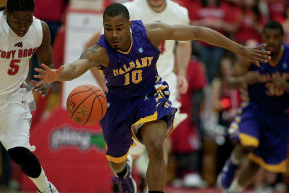 Mike Black of UAlbany stretches out to gather a loose ball against Dave Coley of Stony Brook, during the America East Mens semifinal against Stony Brook at Chase Family Arena in Hartford, CT on March 4, 2012 (Shane Bufano/Special to the Times Union). Photo: Shane Bufano