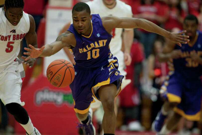 Mike Black of UAlbany stretches out to gather a loose ball against Dave Coley of Stony Brook, during