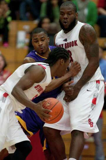 Mike Black of UAlbany defends Dave Coley as he is picked by Dallis Joyner, during the America East M